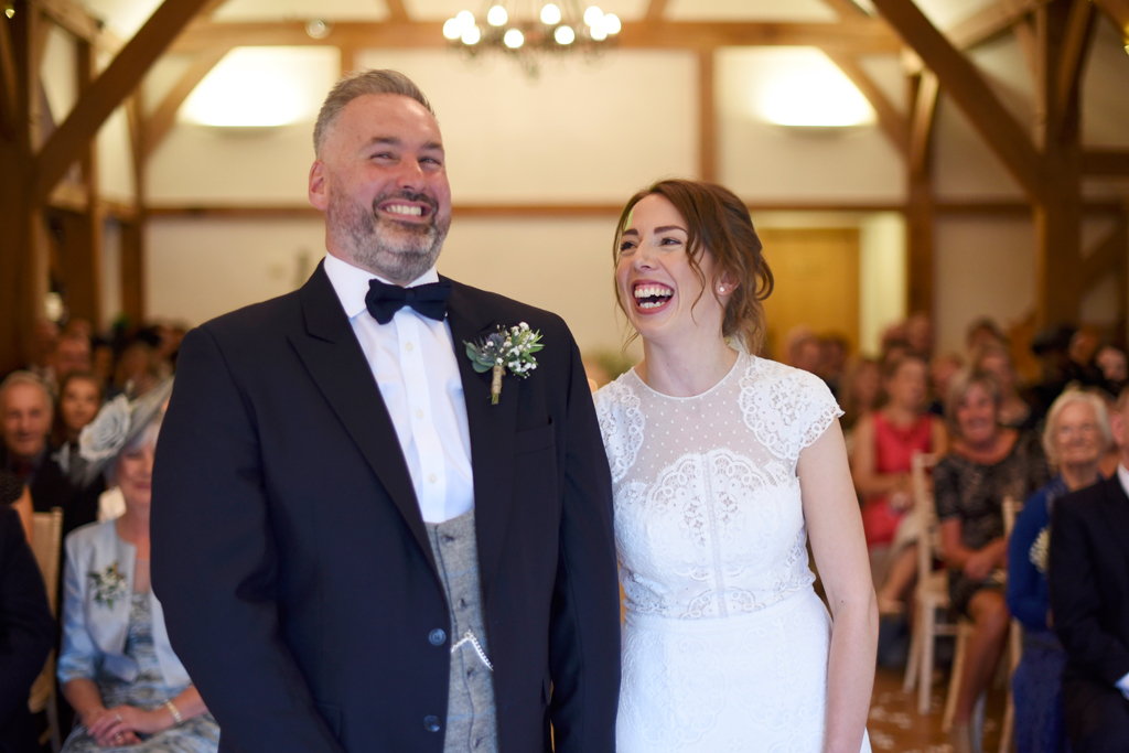The happy newlyweds have a giggle at their wedding ceremony at Sandhole Oak Barn