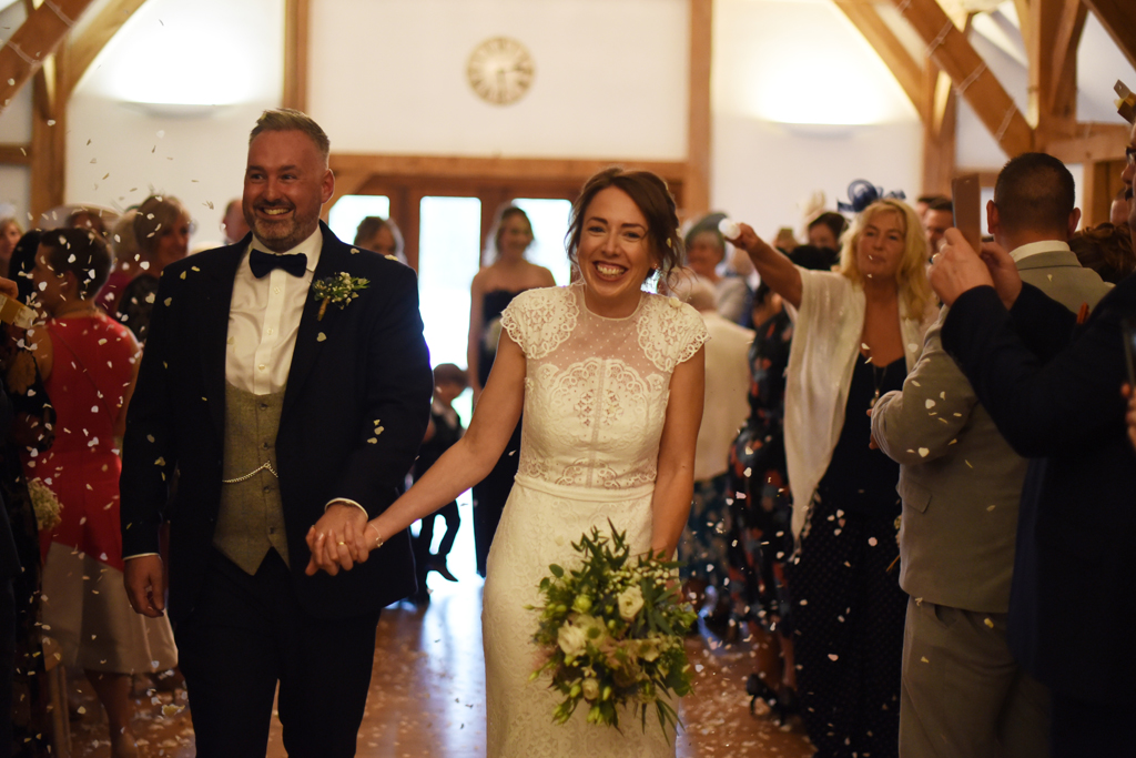 The happy newlyweds have confetti thrown over them