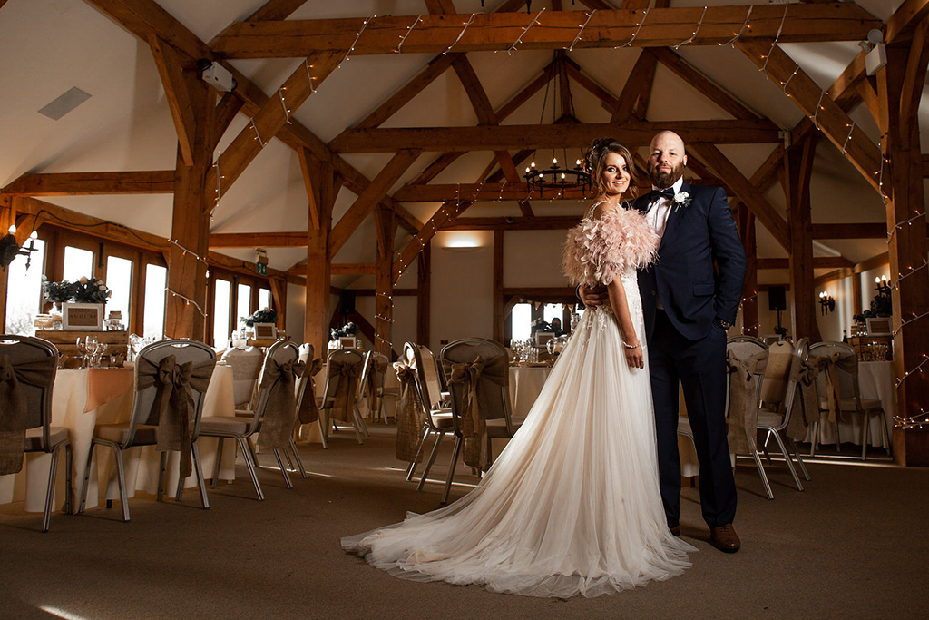 The happy couple pose for a wedding photo in the Oak Barn at Sandhole in Cheshire
