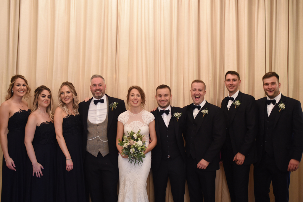 The happy newlyweds pose for a wedding photo with the wedding party at Sandhole Oak Barn