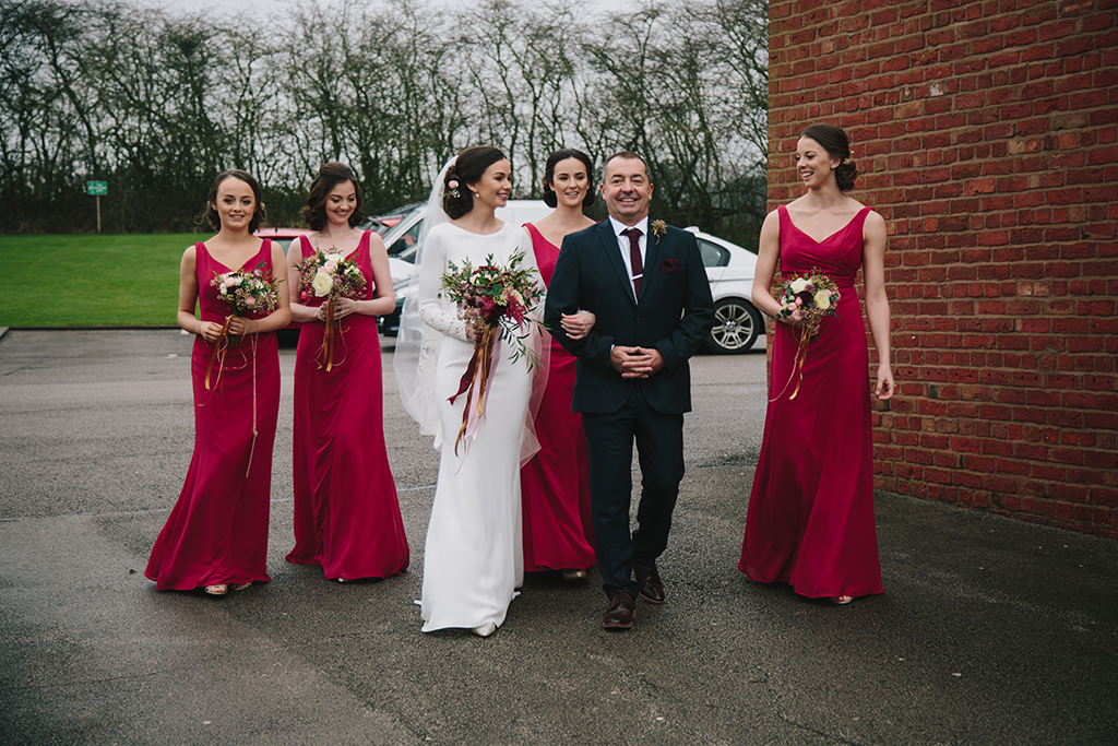 The bride wore a stunning sleeved bridal gown with a veil and her bridesmaids wore deep pink dresses at this barn wedding in Cheshire