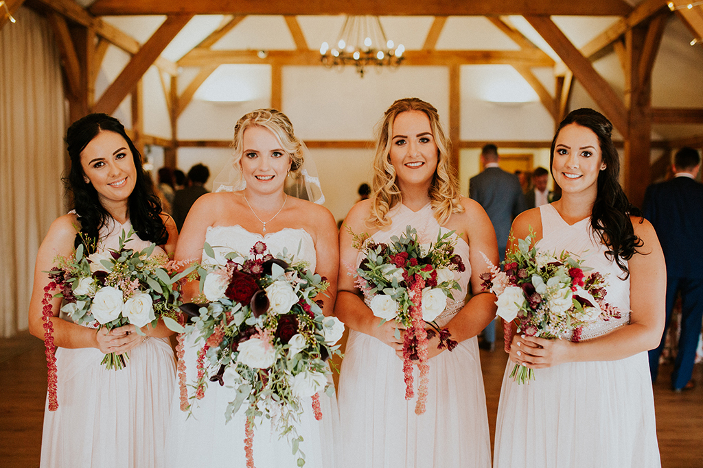 The bride stands with her bridesmaids who all wore light pink bridesmaid dresses