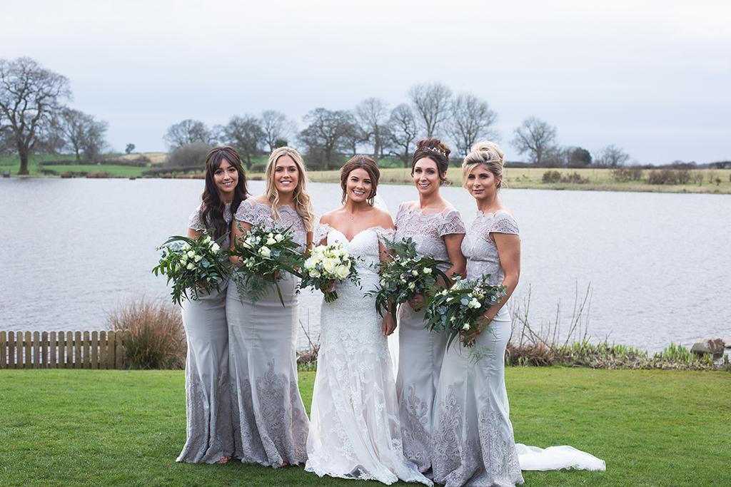 The bride wore a stunning off-the-shoulder-lace-dress while her bridesmaids wore beautiful silver dresses with lace detail at this rural barn wedding in Cheshire