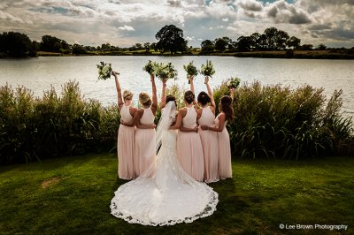 The bridesmaids wore pastel pink wedding dresses and the brides dress had a beautiful lace train at this waterside wedding barn in the North West