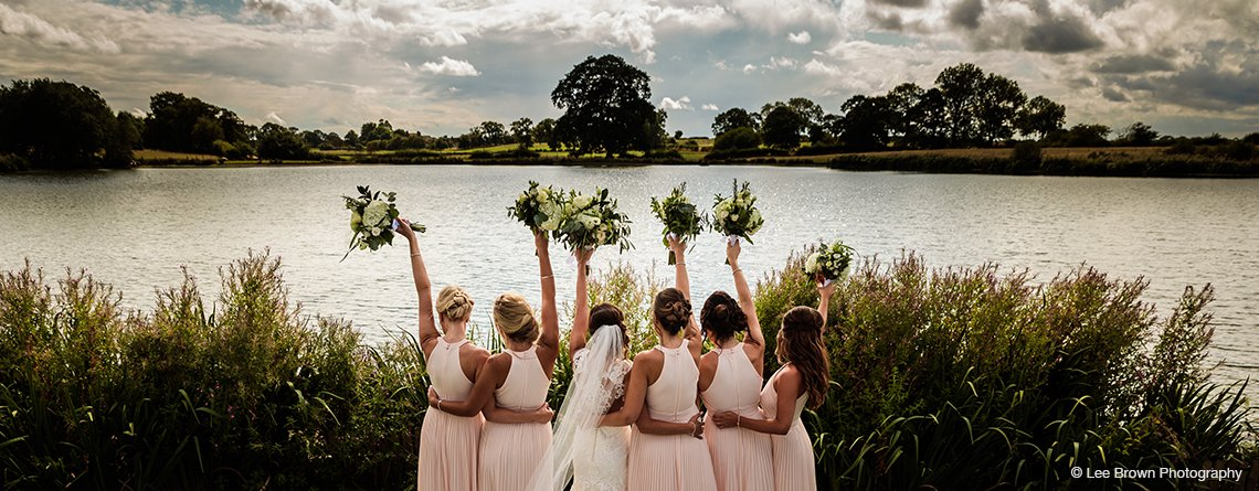 The bride and her bridesmaids have wedding pictures taken with the stunning views as a backdrop at Sandhole Oak Barn.