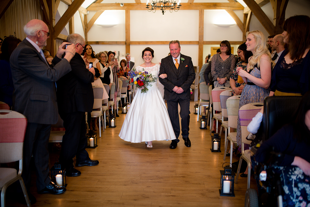 The bride walks down the aisle with her father before the wedding ceremony at Sandhole Oak Barn