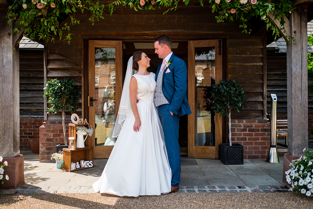 The bride and groom pose for a photo at the entrance to the oak barn at Sandhole Oak Barn