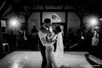 The bride and groom enjoy their first dance on the twinkly dance floor while their guests look on at this rustic wedding venue in Cheshire