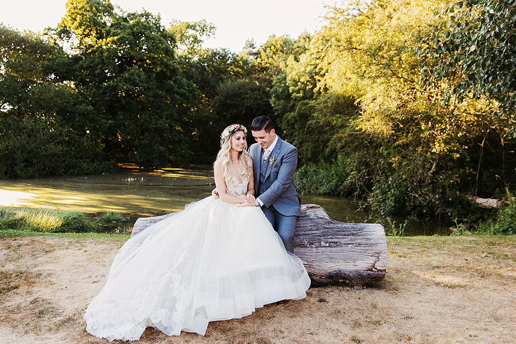 The happy newlyweds pose for a photo in the sunshine at this rural barn wedding in Cheshire