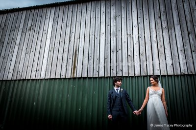 The happy bride and groom hold hands in front of the green barn and pose for their wedding pictures at Sandhole Oak Barn.
