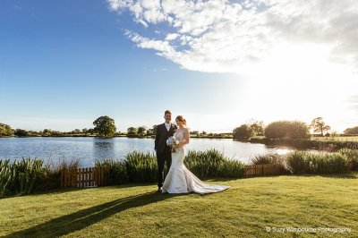 The bride and groom have their picture taken in front of the beautiful lake at Sandhole Oak Barn in Cheshire