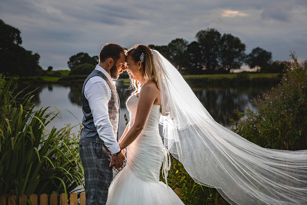 The bride and groom have their photo taken in front of the lake at Sandhole Oak Barn in the North West