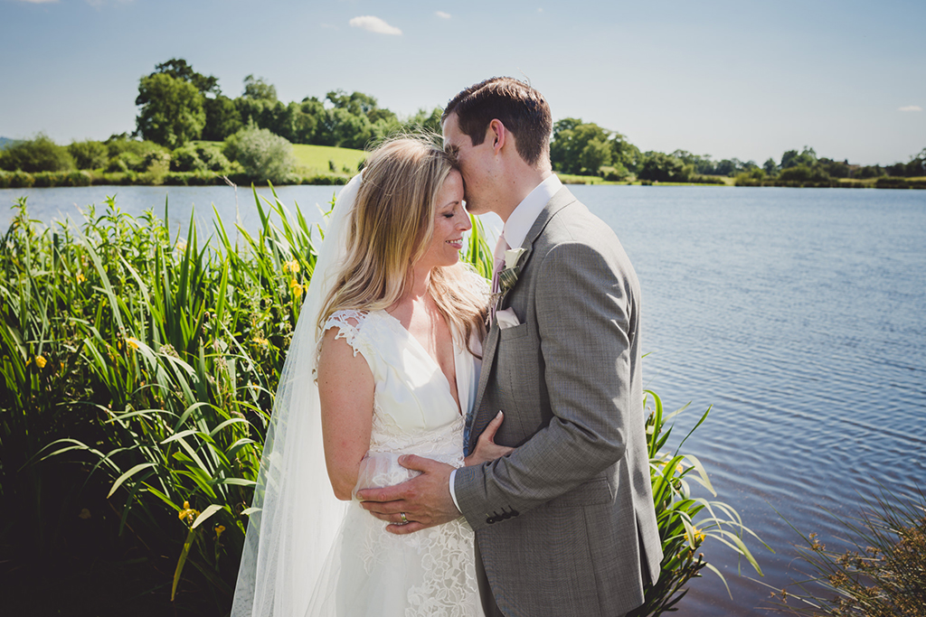 The happy couple have a romantic photo taken at the lakeside at Sandhole Oak Barn