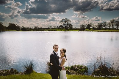 The bride and groom pose for a photo in front of the beautiful lake at this waterside wedding barn in Cheshire