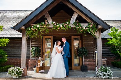 The happy couple have a photo taken at the entrance to the barn surrounded by pretty floral decorations at their North West barn wedding