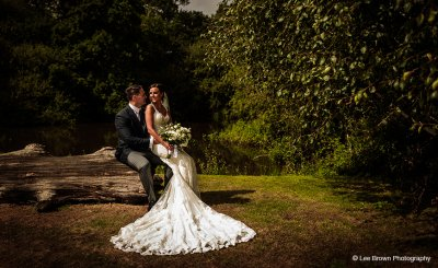 The bride in her stunning wedding gown poses for a photo in the outdoor space at Sandhole Oak Barn in Cheshire