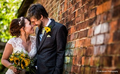 Sunflowers were used for the bride's bouquet and the groom wore a sunshine yellow gerbera buttonhole at Sandhole Oak Barn