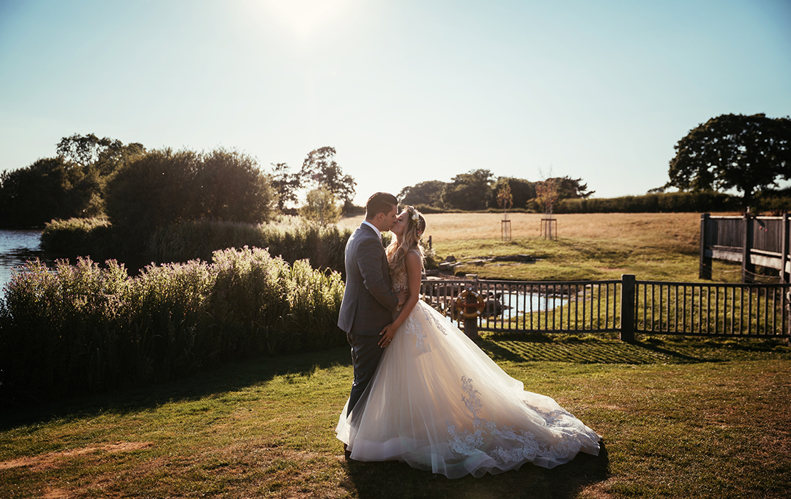 The happy newlyweds pose for a wedding photo as the sun sets at their summer wedding at Sandhole Oak Barn