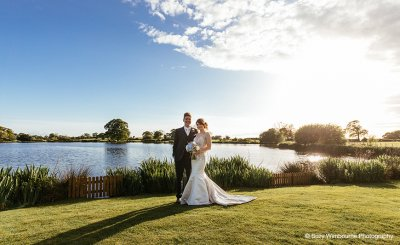The bride and groom pose for a photo at this waterside wedding venue near Manchester
