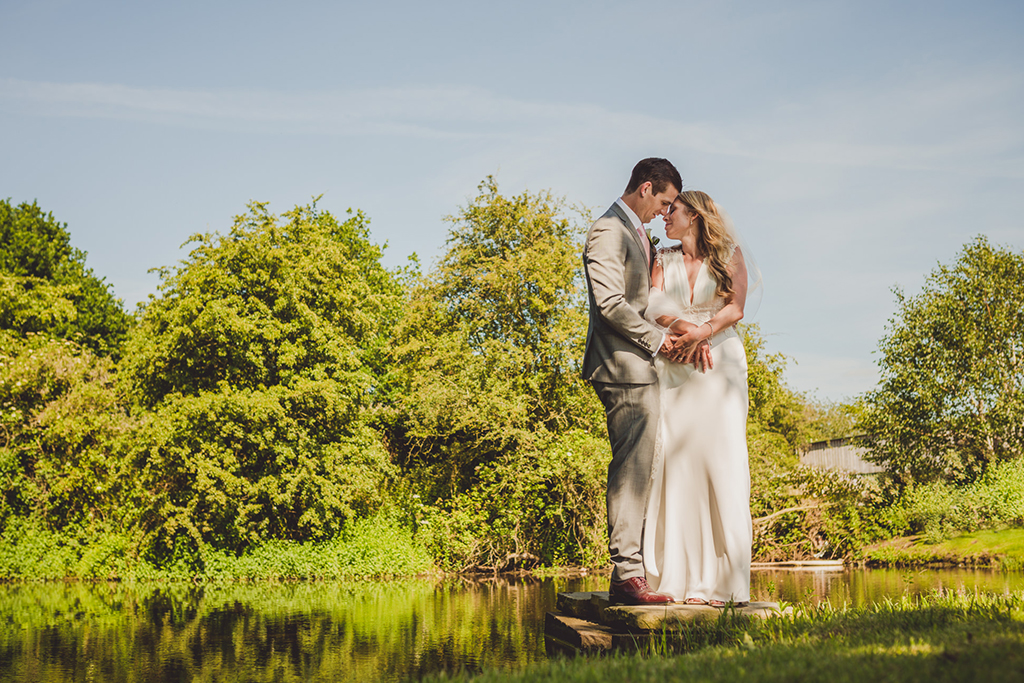 The bride and groom pose for a photo at the waterside of this barn wedding venue