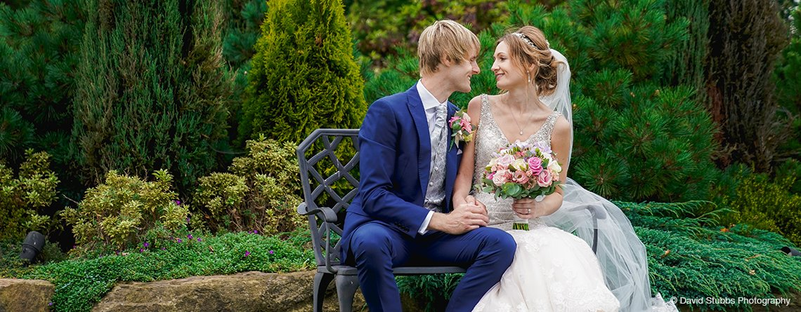 The bride and groom have wedding pictures taken in the gardens at Sandhole Oak Barn in the North West