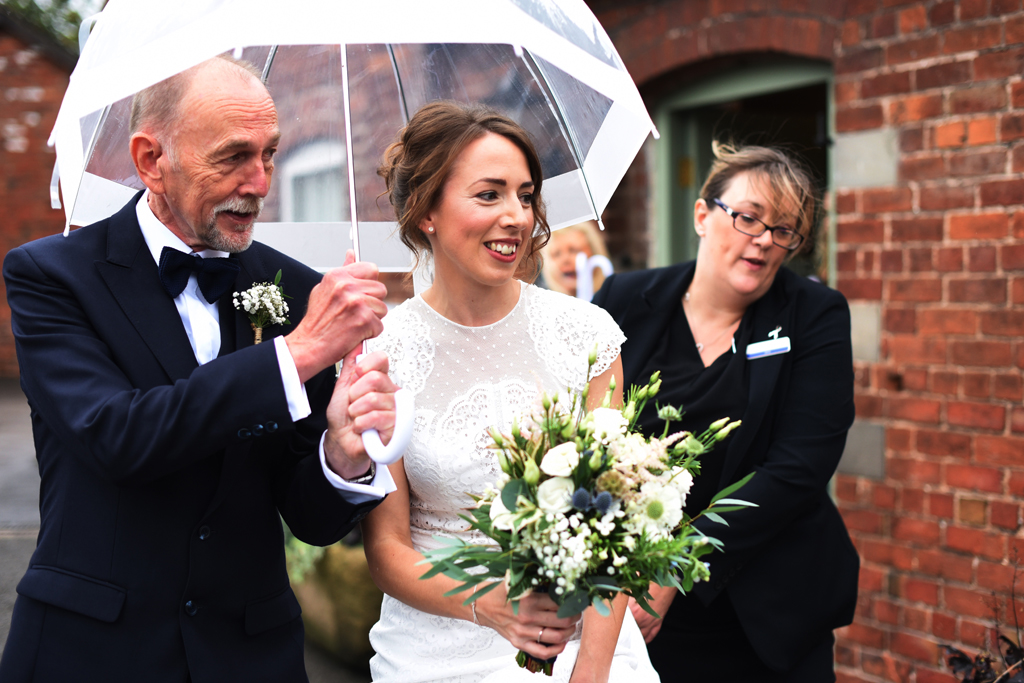 The happy bride walks to the wedding ceremony at Sandhole Oak In Cheshire