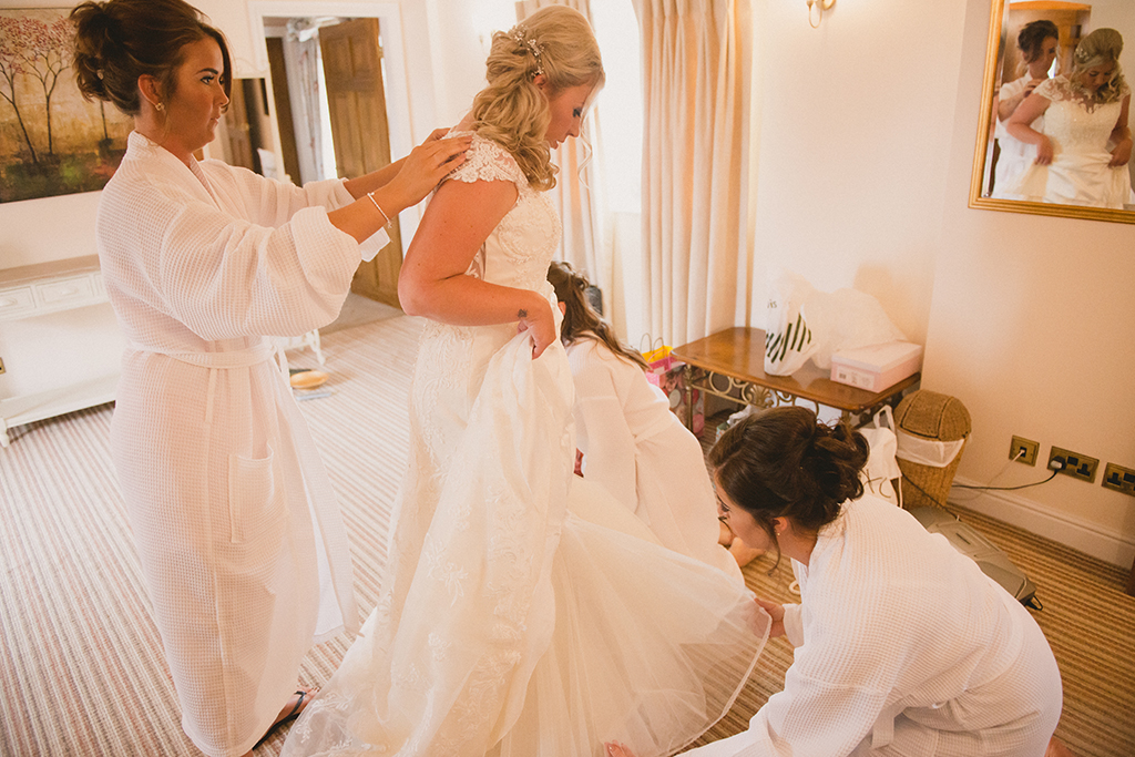 The bride steps into her wedding dress whilst her bridesmaids are on hand to help