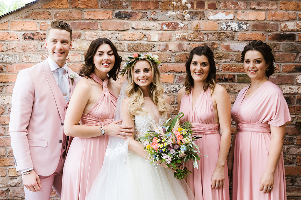 The bridesmaids wore pastel pink dresses and the bridesman a pastel pink three piece wedding suit at this barn wedding in Cheshire