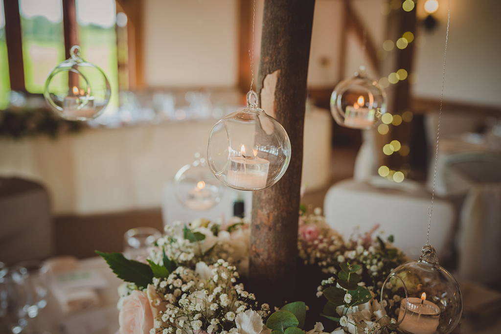 Elegant clear baubles filled with candles were used to decorate this barn wedding at Sandhole Oak Barn in Cheshire