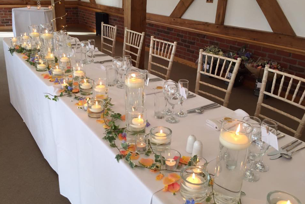 The top table was decorated with candles and tealights with pretty petals and ivy at this North West wedding venue
