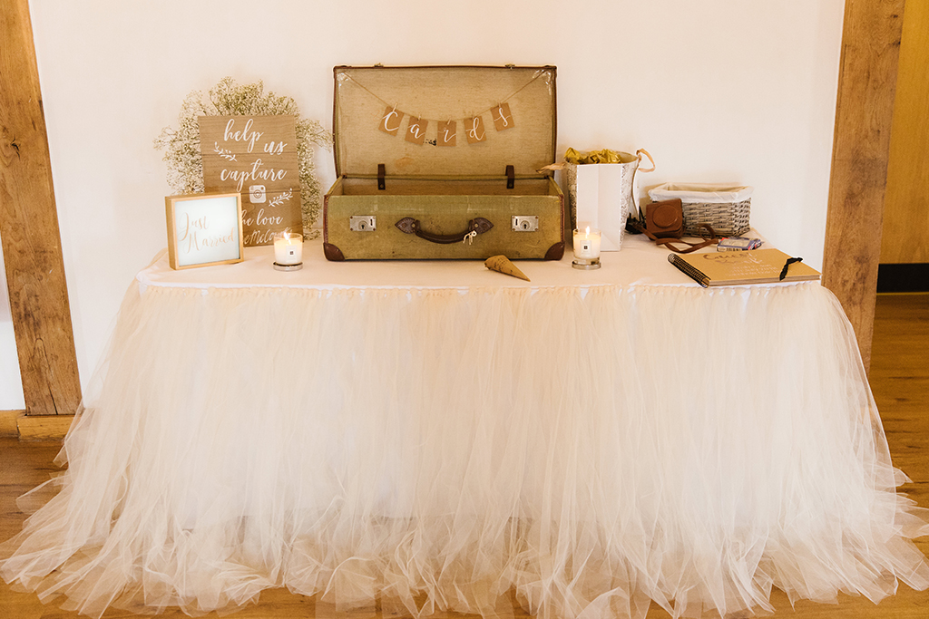 The bride chose a pretty white tulle skirt to decorate the card and message table at her wedding at Sandhole Oak Barn