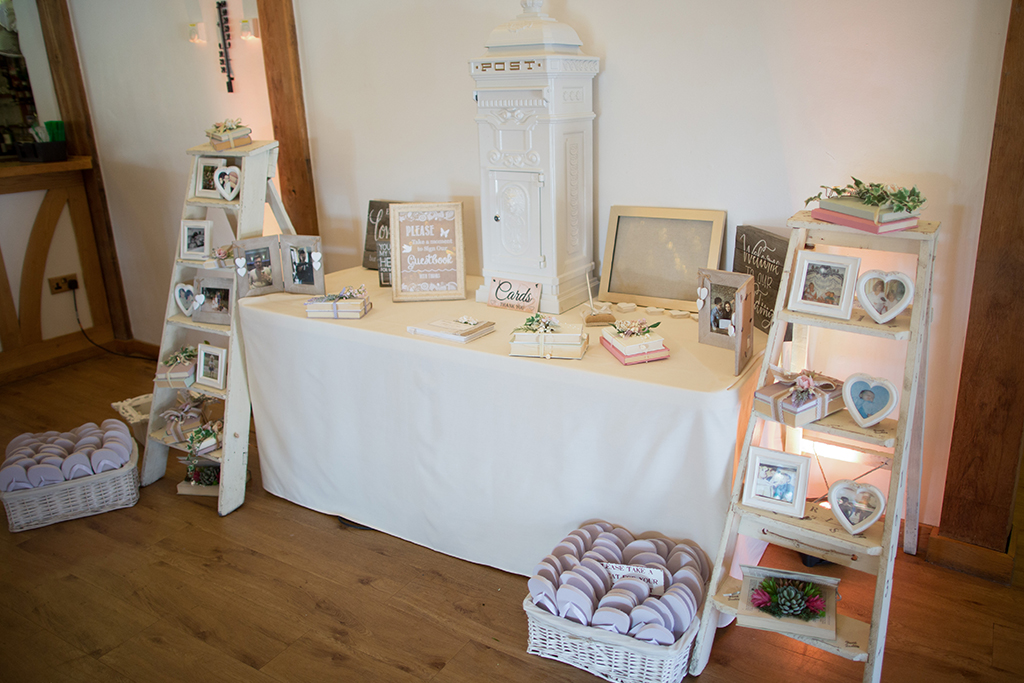 The card table at this spring wedding was decorated with lots of soft white wedding decorations at Sandhole Oak Barn in Cheshire