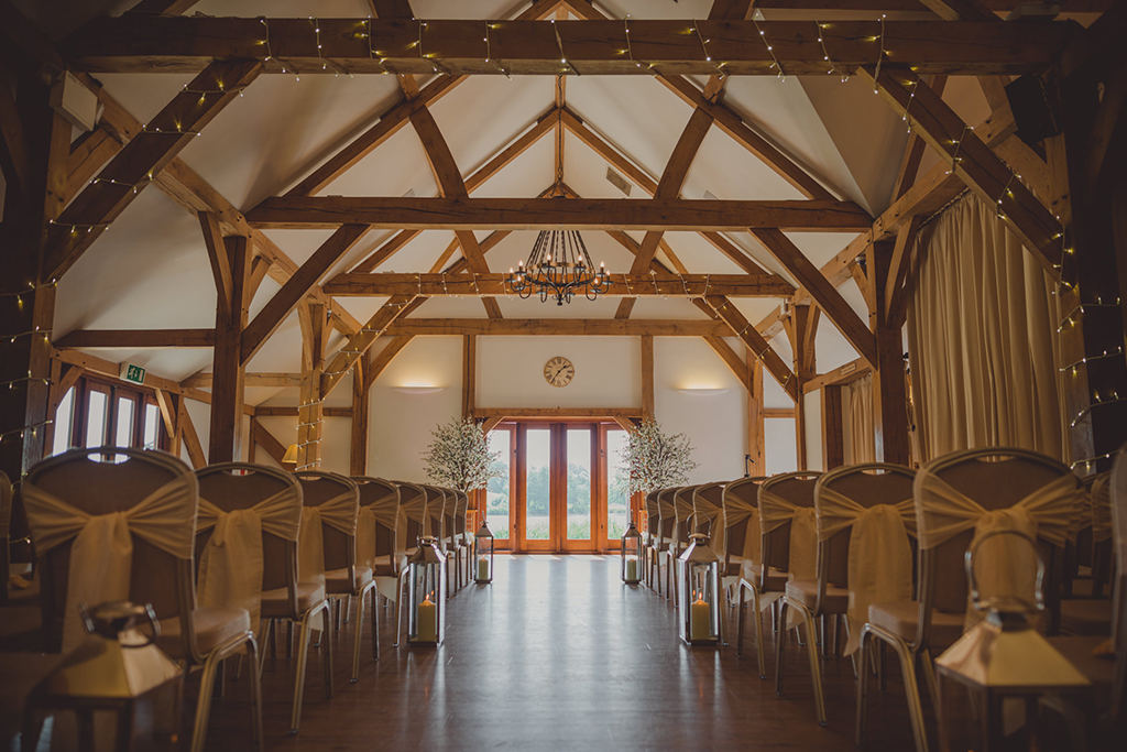 The barn was set up for the wedding ceremony with pretty fairy lights around the beams and lanterns down the aisle