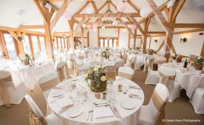 The chairs were covered and decorated with natural hessian sashes to coordinate with the pretty wedding flowers and log slices at this barn wedding in Cheshire