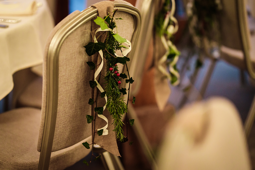 Decorate chairs with arrangements of festive ivy and red berries for that wonderfully wintery feel at your winter wedding at Sandhole Oak Barn