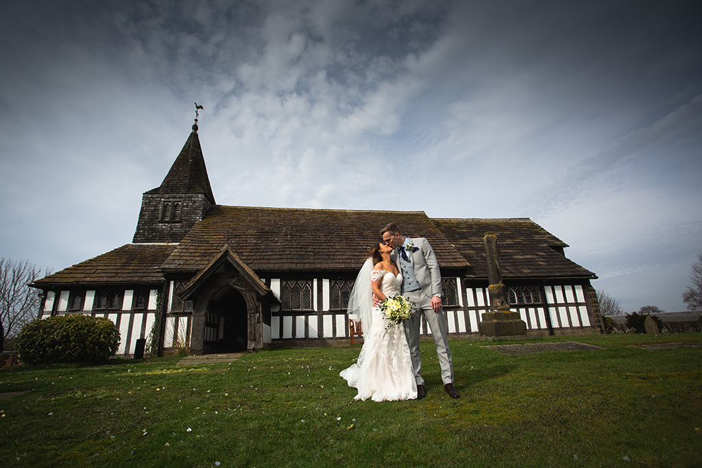 The bride and groom pose for a wedding photo in front of St Paul's church at this barn wedding in Cheshire