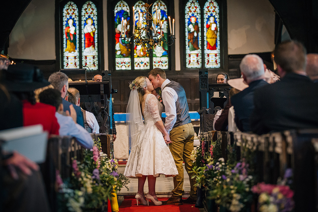 The bride and groom share their first kiss as husband and wife at their church wedding in Cheshire
