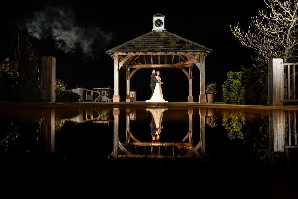 The happy couple pose for an evening wedding photo by the clock tower at Sandhole Oak Barn
