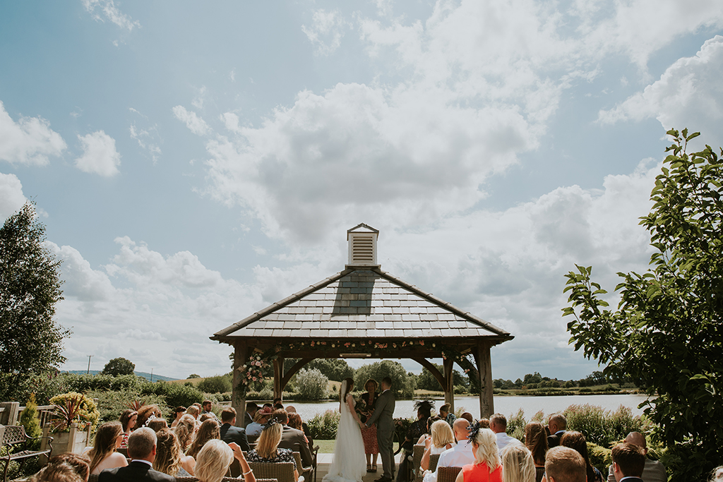 The bride and groom say their vows under the Clock Tower on a beautifully sunny day at this barn wedding venue in Cheshire