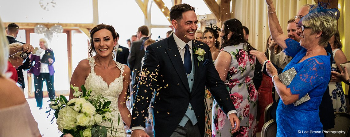 Guests throw natural confetti petals over the newlyweds at this wedding barn in Staffordshire