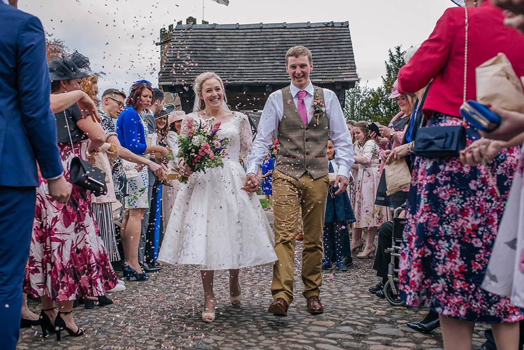 The happy newlyweds have confetti thrown over them at their Cheshire wedding
