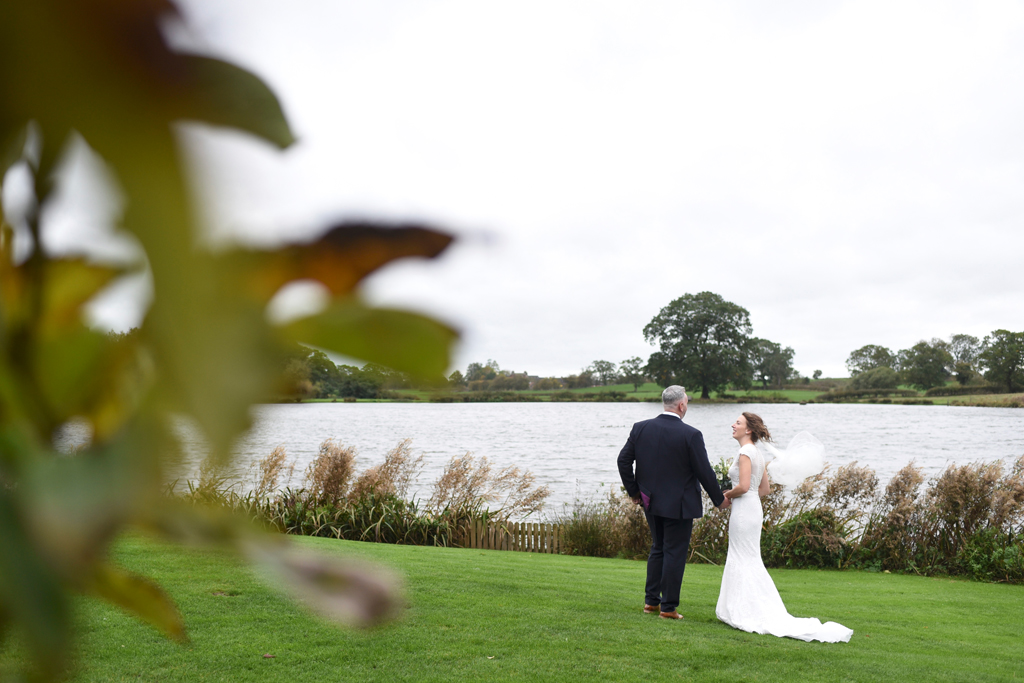 The happy couple take a stroll alongside the lake at this waterside wedding venue in Cheshire