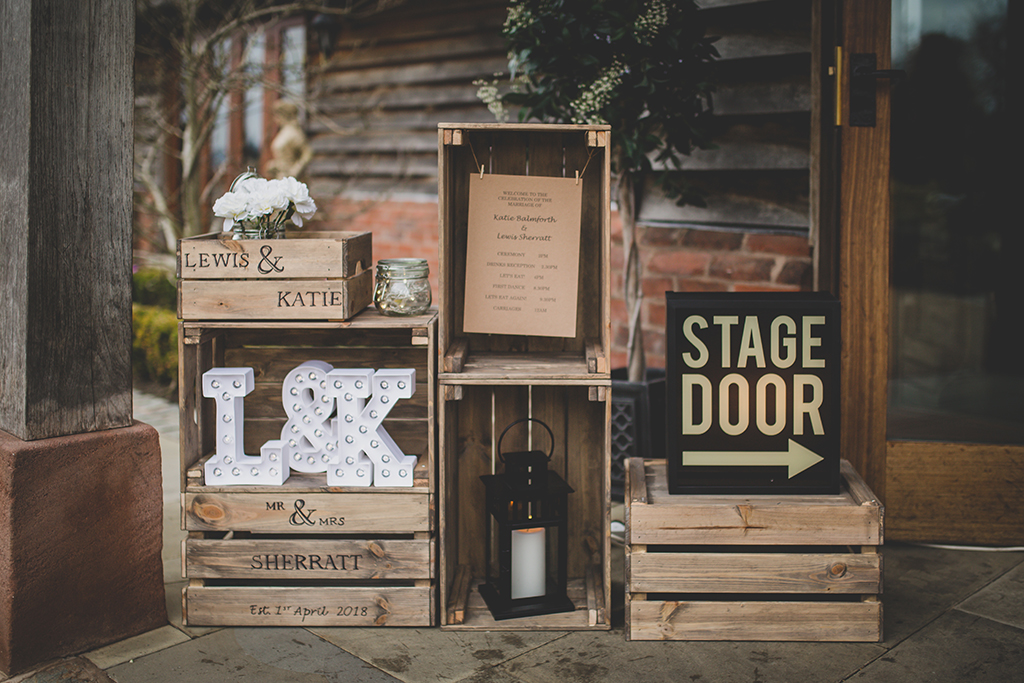 The couple created a display using personalised wooden crates at their barn wedding at Sandhole Oak Barn