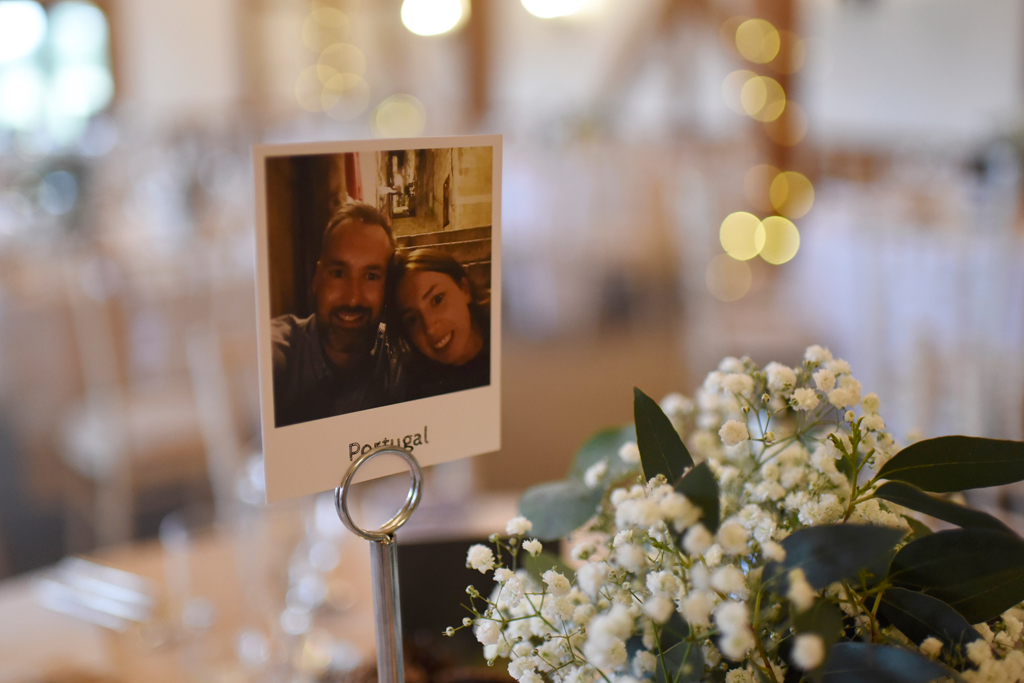 The couple chose photos of themselves in place of table numbers at this barn wedding in Cheshire