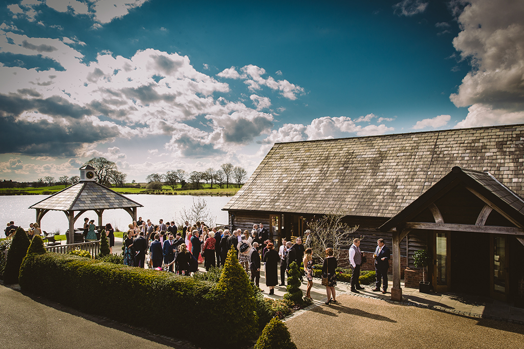 The wedding guests enjoy the reception drinks in the sun at this barn wedding in Cheshire
