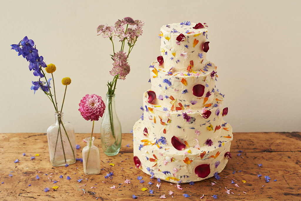 This three-tier wedding cake has been iced with butter cream and decorated with edible flowers