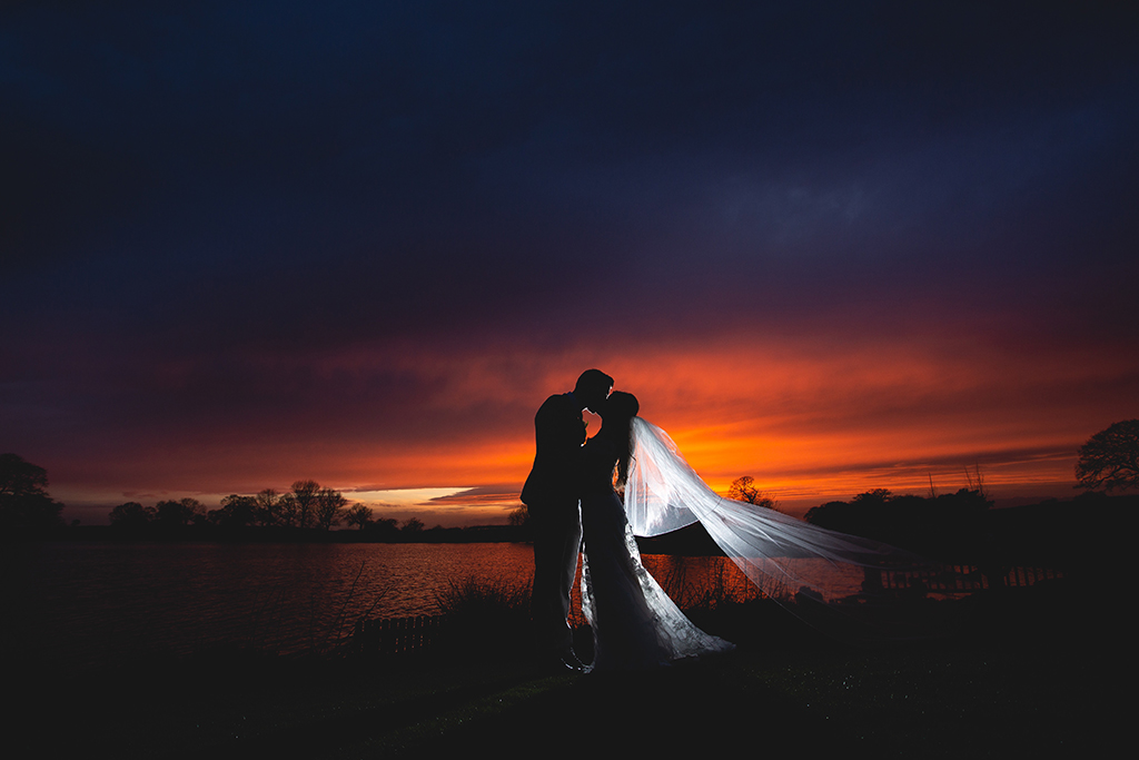 The bride and groom pose for a dramatic sunset shot with the lake as a beautiful backdrop at Sandhole Oak Barn