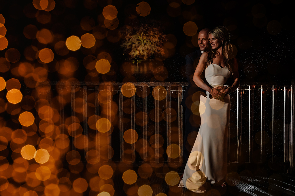 The happy newlyweds pose for a creative evening wedding photo with twinkly fairy lights in shot at Sandhole Oak Barn