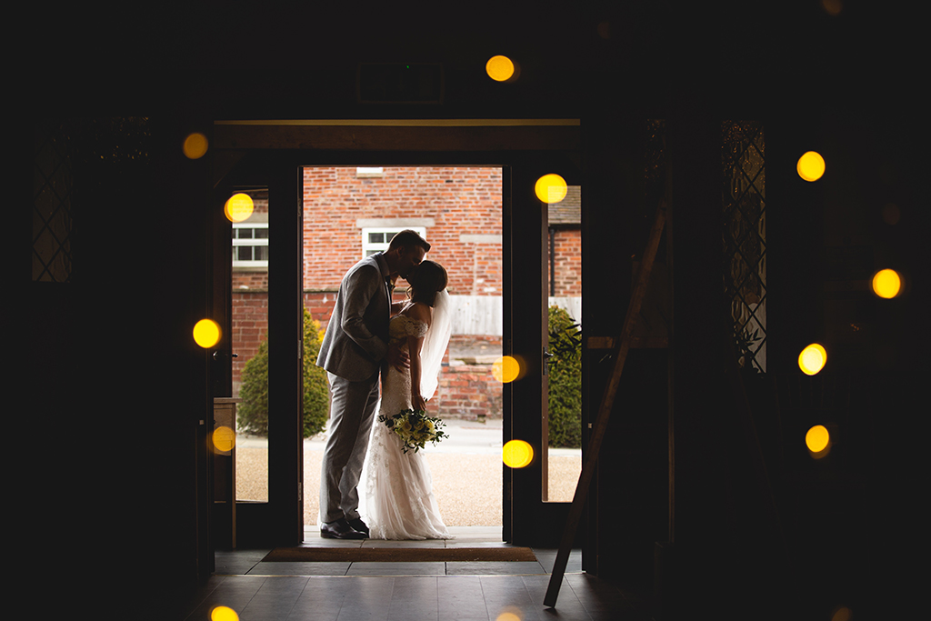 The bride and groom pose for a wedding photo in the doorway of the Oak Barn at Sandhole Oak Barn an exclusive wedding venue in Cheshire