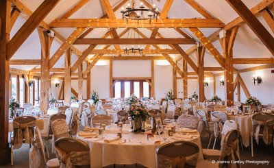 Fairy lights adorned the wooden beams and chairs were decorated with pretty lace sashes at this barn wedding near Manchester